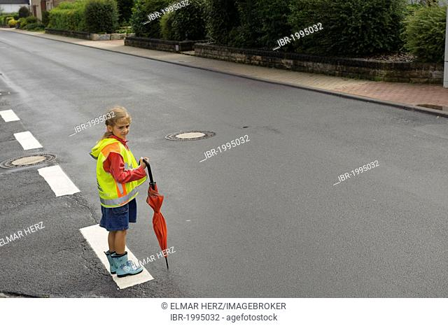 7-year-old girl with yellow safety vest for school children waiting to cross the wet main street, Assamstadt, Baden-Wuerttemberg, Germany, Europe