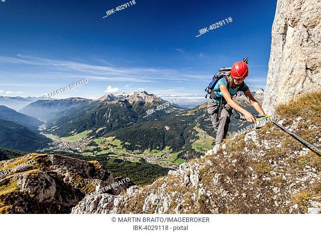 Mountaineer during the ascent to Cima Valacia on the Via Ferrata F. Gadotti in the Val San Nicolo di Fassa, in the back of the Latemar