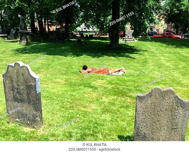 Woman in a red dress sunbathing in a park, Halifax, Nova Scotia