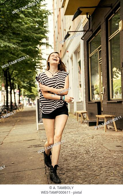 Germany, Berlin, laughing young woman walking on pavement