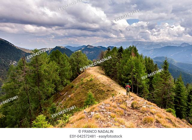 Hiker walks on the mountain ridge under a stormy sky