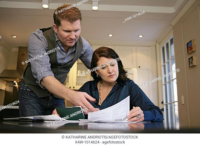 Husband is angry as married couple pays their bills and reviews their finances together