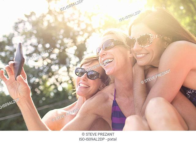 Three mature women in swimwear, taking self portrait