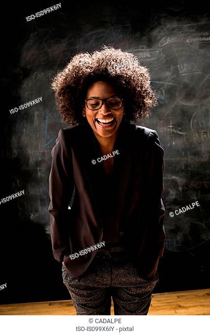 Casual businesswoman by blackboard