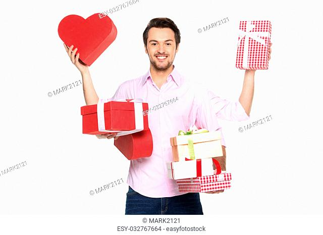 Man holding presents wrapped in gift paper, isolated on white. waist up of guy with four hands holding boxes and smiling