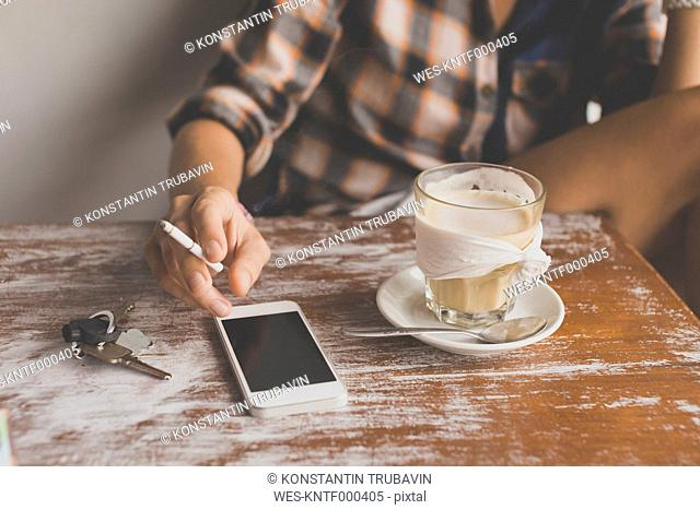 Woman with cell phone in a cafe