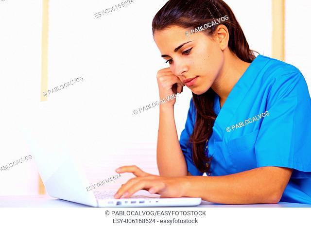 Portrait of a cute young nurse using a laptop