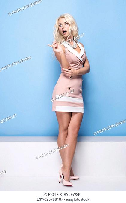 beauty, fashion and young woman in pink dress on blue background pointing her finger to the side empty space