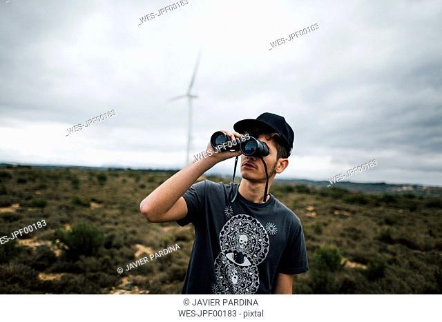 Spain, Lleida, young man looking through binoculars in rural landscape