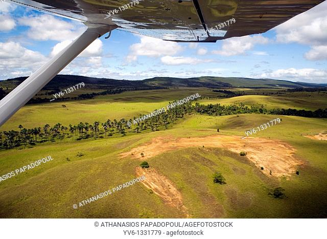 Shoot From Above Of Savanna Land With Chezsna Type Airoplanes Right Wing Noticeable At The Top Of The Photograph Shoot On A Bright Sunny Day With Blue Sky And...