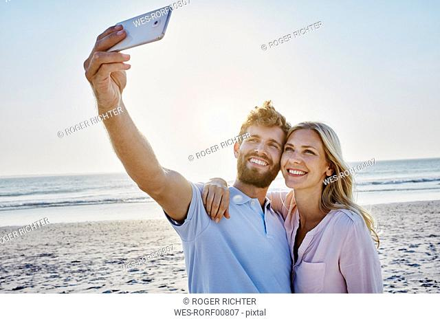 Happy couple taking a selfie on the beach
