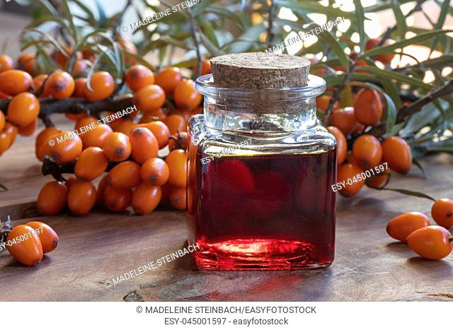 A bottle of sea buckthorn oil with fresh berries on a table