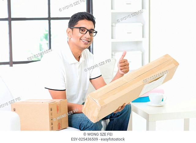 Indian guy received an express parcel and giving thumb up at home. Asian man sitting on sofa indoor. Courier delivery concept