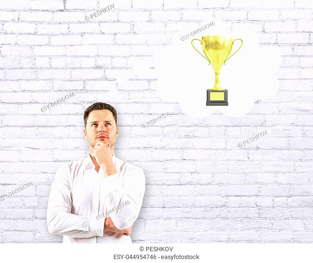 Handsome businessman thinking about golden cup trophy on white brick background