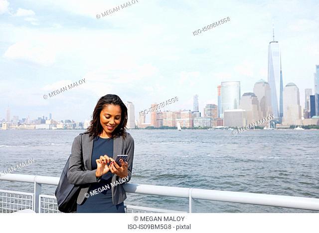 Businesswoman using cellphone, New York City skyline in background
