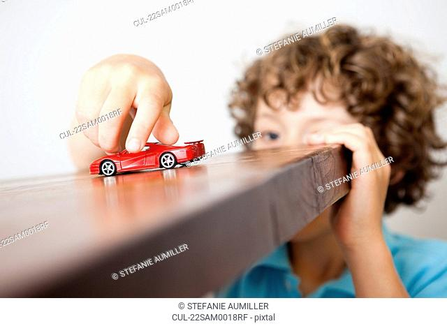 Boy playing with small red car
