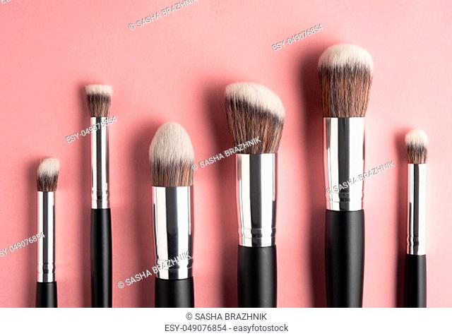Creative concept beauty fashion photo of cosmetic product make up brushes kit on pink background