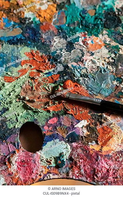 Detail of messy artist palette and paintbrush in artists studio, close up