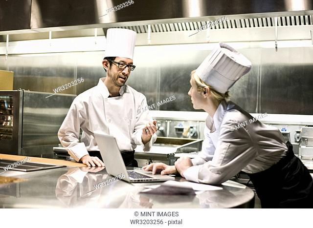 A mixed race pair of chefs working with a laptop computer in a commercial kitchen