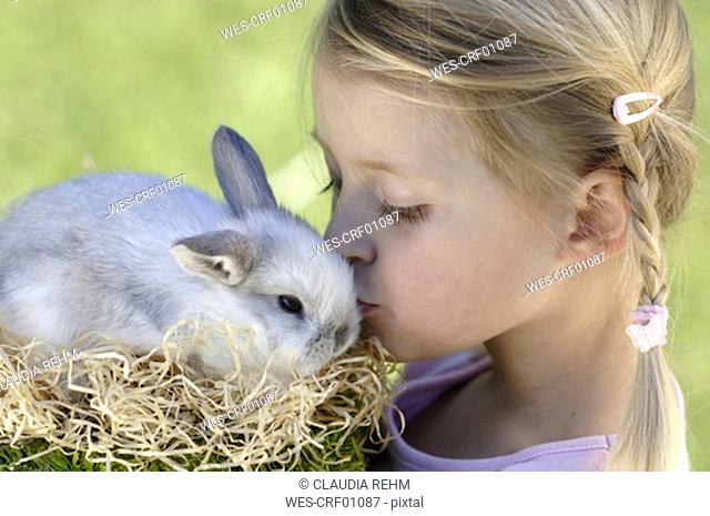 Girl kissing easter bunny, close-up, portrait
