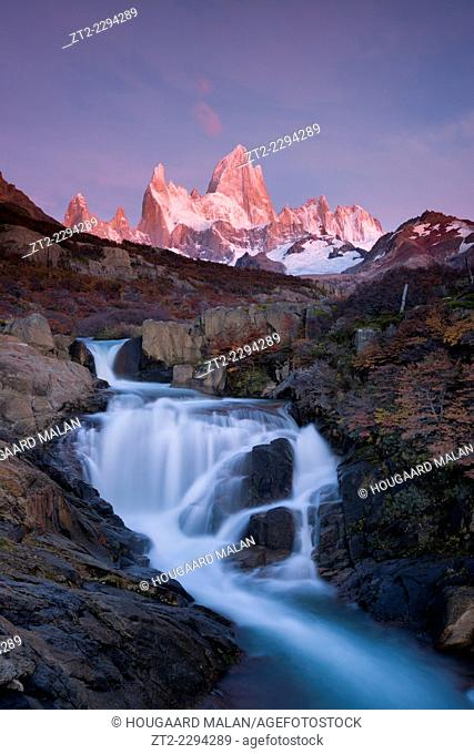 Landscape photo of a waterfall below mount Fitz Roy under a pink sunrise sky. El Chalten, Patagonia, Argentina