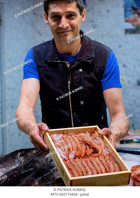 Man presenting a wooden box with prawns