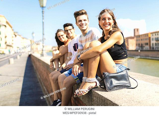 Italy, Pisa, group of four happy friends sitting on a wall along Arno river
