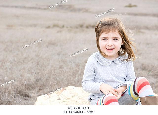 Portrait of girl sitting on rock