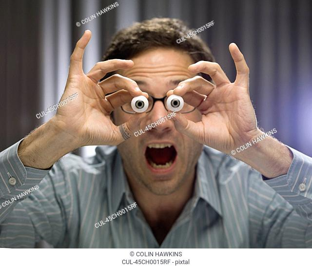 Businessman holding glass eyes