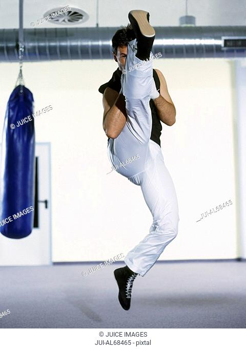 Portrait of a female boxer doing a high kick