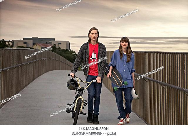 Teenagers with bicycle and skateboard