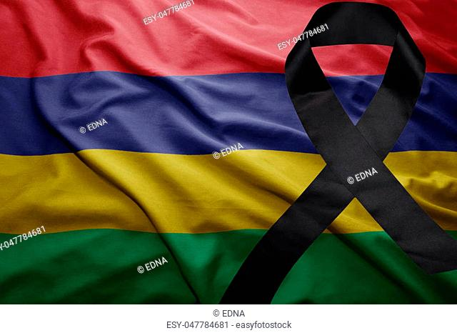 waving national flag of mauritius with black mourning ribbon
