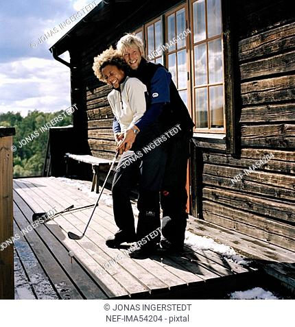 A man teaching a woman how to golf Sweden