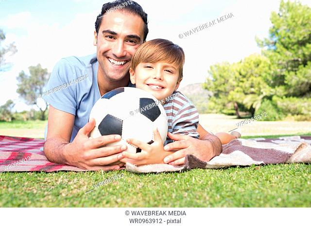 Portrait of happy father and son on picnic blanket with a football