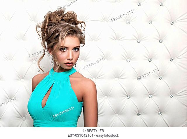 Studio portrait of a sexy blond in blue dress, over leather upholstery background. Elegant luxury woman with a seductive neckline and bare shoulders looks into...