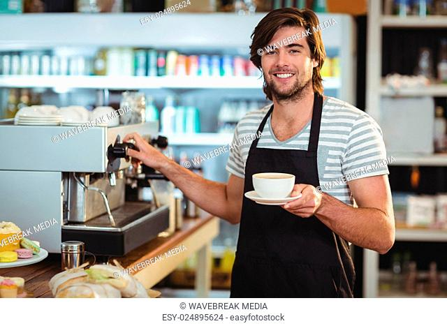 Portrait of smiling waiter holding cup of coffee