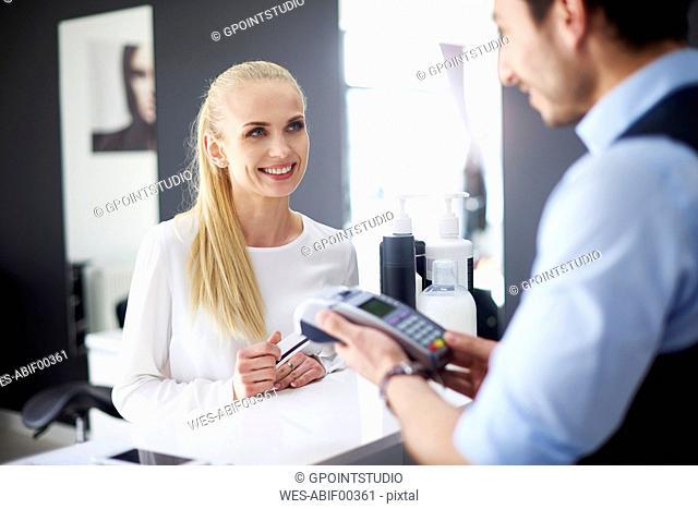 Woman paying at hair salon