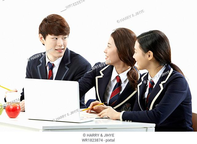 Three students in school uniforms working together