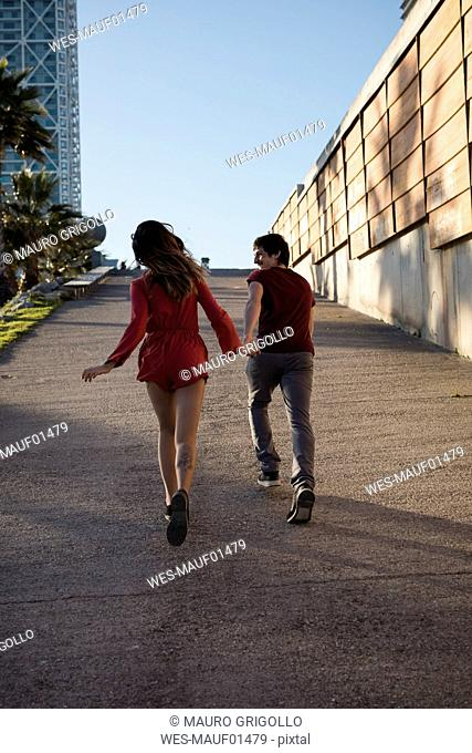 Spain, Barcelona, couple running hand in hand in the city