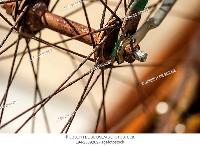 Rusty spokes and wheel hub of an old bicycle