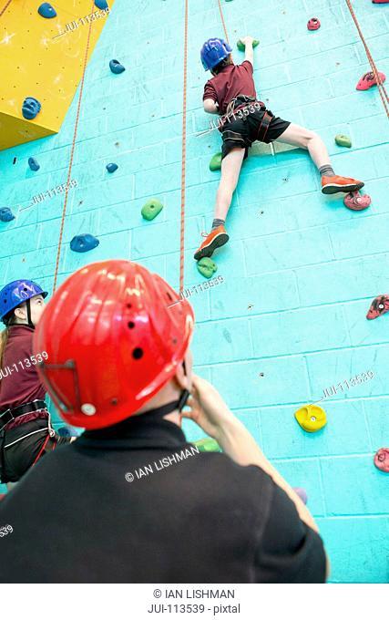 Gym teacher watching high school student climbing rock climbing wall