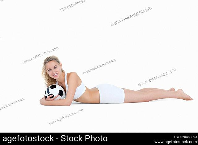 Smiling teenager holding a football close to her