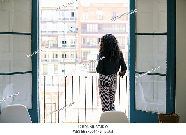 Young woman standing on balcony, looking at view
