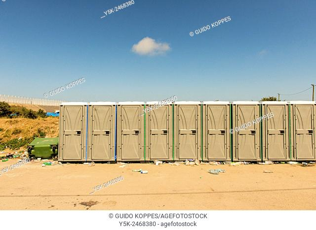 The Jungle, Calais, France. Queue or row of mobile toilets in the refugee camp for illegal immigrants, just north of town