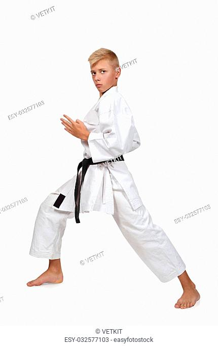 Young boy training karate in white kimono and black belt