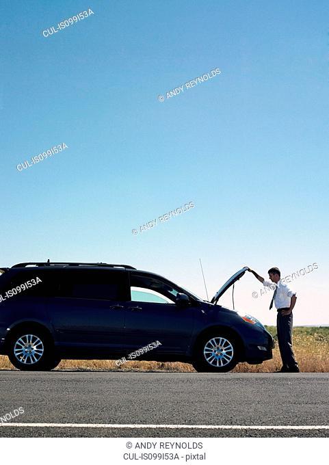 Man looking under hood of broken down car
