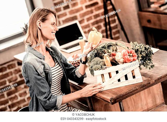 Tasty vegetable. Delighted positive young woman sitting at the table and looking at the pepper while taking it from the box