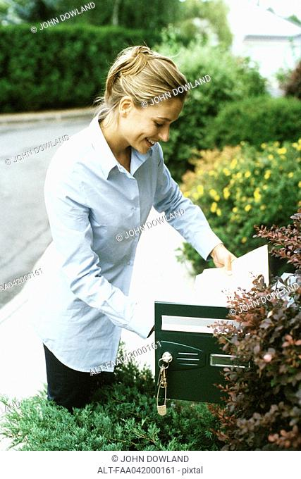 Woman checking mail, smiling