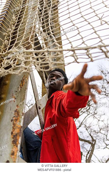Young man reaching out, under volleyball net