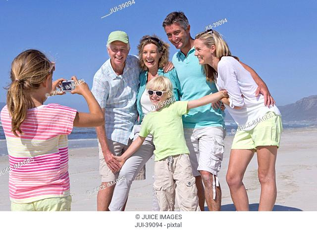 Girl with digital camera photographing multi-generation family on sunny beach